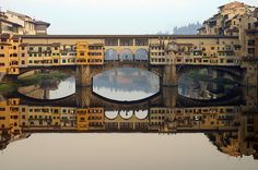 The Ponte Vecchio is a medieval bridge over the Arno River. Actually, it's much more than a bridge – it's a street, a marketplace, and a landmark of Florence, Italy. The Ponte Vecchio that we know today was built in 1345 by Taddeo Gaddi after an older span was destroyed in a flood. In 1565, Duke Cosimo I de Medici ordered an architect named Giorgio Vasari to construct a roofed passageway. Centuries of haphazard additions gave the bridge's distinctive, irregular appearance today. Isn't it…