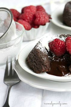 A rich chocolate cake with a gooey middle topped with powdered sugar and fresh raspberries: Gluten-free Chocolate Molten Cake.