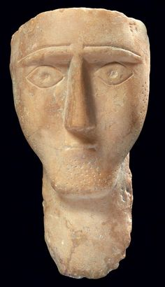 Stele, face of a man with triangular nose above a pinched mouth, incised eyes. Alabaster, South Arabian peninsula, 3rd-2nd century BV