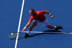 Alex Bogomolov Jr. of Russia stretches to play a forehand against Andy Murray of Great Britain during their men's singles first round match on Day One of the 2012 US Open