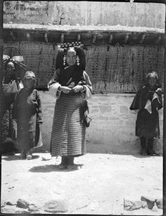 Photographer: Rabden Lepcha?, Collection: Sir Charles Bell, Date of Photo: 1920-1921, Region: Lhasa. Woman, seated, wearing a Lhasa-style head dress and with a charm box on her chest; fur-lined outer garment.
