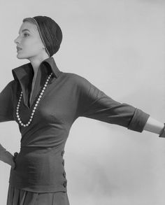 Cherry nelms in a long-torso jersey top with deep high-rolling collar (from VOGUE pattern), buttons at hips, cloche, and pearls, 1949  Photo by Horst P. Horst