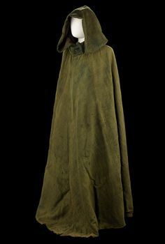Boat cloak, circa 1805 although quite faded, it is an extremely rare survival of protective or outdoor clothing from the early part of the 19th century. It is made of a hard wearing, coarse weave green wool and lined with a similar brown wool. The cloak, which is quite voluminous, gathers into a stand or fall collar and fastens with a small Royal Naval button at the neck.