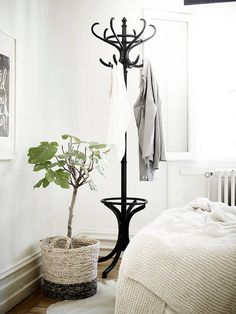 Classic black coat stand in the corner of a bedroom in a Swedish space in neutrals. . Stadshem.