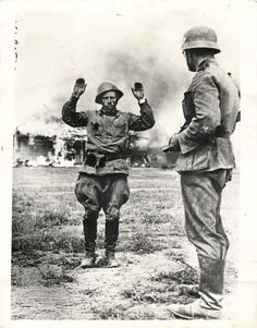 1941- Nazi trooper taking a Russian soldier prisoner after he was caught trying to escape from blazing building (background), from which the Nazi guns have driven the Russian defenders.