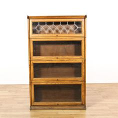 This lawyer's barrister bookcase is featured in a solid wood with a glossy light oak finish. This bookshelf display has 4 shelf tiers, lift up glass doors and diamond mullion accents. Perfect for storing textbooks! #americantraditional #storage #bookcase&shelving #sandiegovintage #vintagefurniture