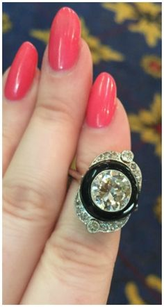 This Art Deco-esque ring (exact age unknown) features a perfect black onyx circle surrounding a 2.05 carat circular cut diamond on a platinum, diamond embellished shield-like setting. At Simon Teakle.