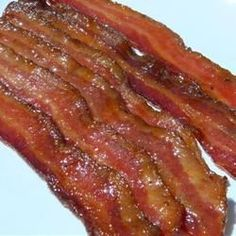 Smoky bacon is baked with a brown sugar and maple syrup glaze for a crunchy and sweet party snack.