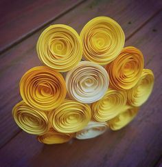 This paper flower bouquet encompasses 12 mini yellow and ivory rolled paper flowers, made entirely from 100% recycled paper. The specialty