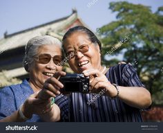 Two women embracing outdoors with camera