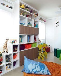 A estante com nichos guarda todos os brinquedos, mas se esvazia facilmente: a escadinha de girafa dá uma mão e uns centímetros a mais, se for o caso. Cestinhos coloridos organizam as miudezas. Projeto do escritório Lovisaro Arquitetura e Design