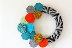 A collection of bright felt flowers juxtaposed with stripes makes this wreath a cheery addition to any room and a natural fit for a kids' room.  Project via http://www.nestofposies-blog.com/