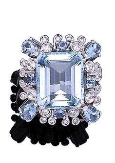 An aquamarine and diamond dress ring The large step-cut aquamarine, within an openwork surround set with pear-shaped and circular-cut aquamarines, and collet-set brilliant-cut diamonds, diamonds approx. 0.35ct total.