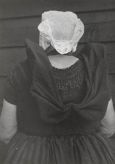 Weduwe De Bei in Axelse streekdracht. Mevrouw De Bei is gekleed in haar zondagse dracht. Ze is in de rouw. Over de zwarte ondermuts met het oorijzer draagt ze een 'ronde muts' of 'hernhutter' (type muts), welke gedragen wordt door meisjes tussen het 7e en 14e levensjaar, en soms door volwassen vrouwen. 1950 #Zeeland #Axel