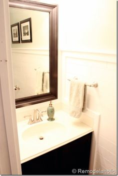 Half bath with DIY plank walls, wrapped in molding, DIY inlaid tile rug, black vanity and pocket door