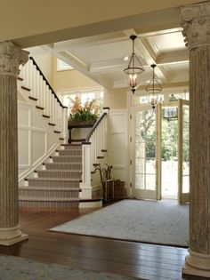 Such a classy space.  Love the staircase, coffered ceiling & architectural detail on the wall.  So open & airy!