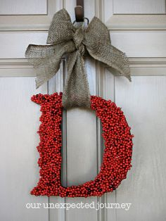Red faux berries can be hot glue gunned onto your family's last name initial, hung on the door with a bow.