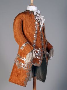 Pumpkin Orange Frock coat and waistcoat with Silver Sequin Embroidery. France, ca. 1750-1760. Silk moiré rib weave ground, silver-colored metallic strip over a white core thread, silver-colored metal sequin, ivory lace at sleeves (probably nineteenth century). Embroidery Types: Couching work, bead work: sequins. (Art of the Embroiderer label copy, 2008)