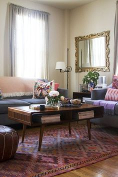 Sofa & armchair combination, colourful rug, coffee table with storage, lamp in corner, big wall mirror, pouffe/ footstool.