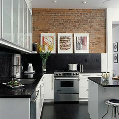Vintage architecture can accommodate modern function. For example, century-old brick provides texture, color, and contrast in a kitchen with otherwise sleek and seamless surfaces. The black granite countertop climbs the wall to become a backsplash and display ledge for the homeowner's art