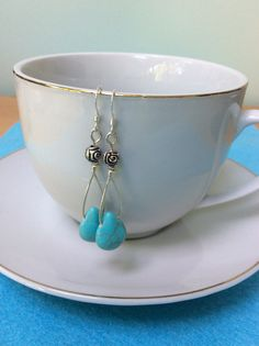 Turquoise with silver plated roses - drop style earrings with sterling silver hooks. Hand twisted silver plated wire was used to join these beautiful turquoise drops to the rose beads. Turquoise is associated with positivity and calmness. Turquoise Bracelet, Silver Plate, Buy And Sell, Wire, Positivity, Sterling Silver, Beads, Bracelets, Hooks
