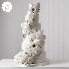 A modern striking sugar flower cascade wedding cake in colours of white, ivory and sage