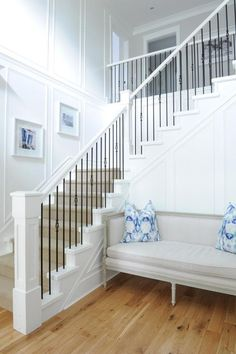 Chic foyer features a white staircase accented with iron spindles lined with a sisal rug. A wainscoted staircase wall is lined with a gray French settee accented with blue pillows.