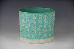A Chinese Brush pot, the circular pot decorated with moulded Chinese character marks against a ge