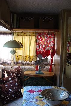Clothespin vintage aprons for curtains in travel trailer.