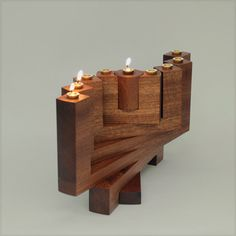 Menorah 360º by OriAroesti on Etsy. A menorah that expands into a variety of different positions in space (made of mahogany with brass candle cups). Very mid-century modernish.