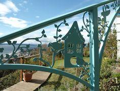 Steel plasma cut birdhouse and vine outdoor railing.