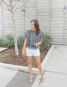 Houston based petite fashion blogger styles white shorts for spring and summer with a super versatile navy and yellow printed top.