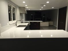 Grey floors espresso cabinets and arctic white countertops. Kohler stainless steel farm sink and GE cafe range and hood.