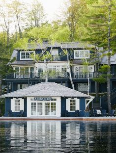 Amazing colonial lake house featuring navy paint, white trim, white shutters, French doors, and second floor terrace alongside the lake | Muskoka Living