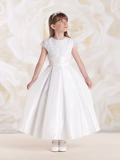 Taffeta, satin and lace tea-length A-line dress with lace illusion cap sleeves, hand-beaded jewel neckline, taffeta bodice features high-low lace overlay and satin covered back buttons, set-in waistband with tieback sash, box pleated circular skirt with built-in crinoline, perfect as a First Holy Communion dress. Sizes: 6 – 14