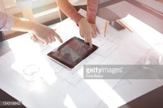 Stock Photo : Business people discussing plans on tablet.