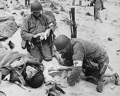 pictures of soldiers | Medics help an injured American soldier on the coast of France