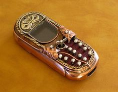 With its leaves, vine design and mother of pearl keys, this cell phone seems perfect for the romantic steampunk fan. The red leather background and copper case provide an interesting color combination and what's especially cool is the little silver ornament for a menu button that looks like a wind-up key. This was Ivan Mavrovic's very first steampunk cell phone creation, created sometime in 2008 — the first of many.
