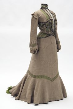 Two-piece natural colored linen dress with green silk underslip. Linen fabric purchased in Cuba by donor and dress constructed by the Misses Leonard, St. Paul dressmakers.  1901-1902