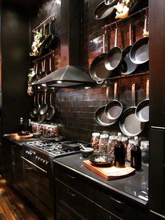 Dark kitchen, pots hanging on the black tiled wall