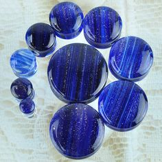 Glass plugs with a streaked blue glitter interior. Quantity: Sold as 1 pair (2 pieces) Style: round cut plug, s sides convex Flare: Double flare Wearable Width: 6mm Size: Size ordered is wearable area
