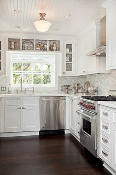 Gorgeous kitchen design with beadboard ceiling, schoolhouse pendant, white flat center panel kitchen cabinets, marble tiles backsplash, polished nickel gooseneck faucet, Wolf Range and sterling silver serveware.