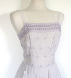 This sweet gauzy cotton 50's dress will be perfect for the hot summmer months. With it's thin straps, airy material and eyelet cutouts you will be ready for a day at the beach in this dress! The eyelet detail is more intricate along the neckline, spaces out through the bodice and also has a trim a few inches up from the hem. The dress zips up the center back.