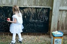 I easily resolved this by making my own chalkboard out of an old door (You could use any piece of old board you might have on hand.)    For this project, you will need to head to the craft store and buy a cheap container of chalkboard paint. Follow the directions on the paint. Once dry, hang your board, buy a $1 bin of sidewalk chalk and let the kids go nuts!