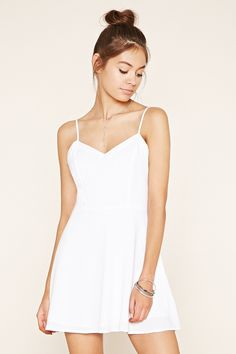 This woven fit and flare dress features adjustable cami straps, geo-shaped back…
