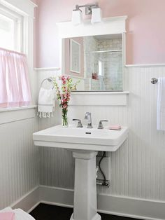 Pale Pink + Bright White - This bathroom gets its romantic and feminine feel from pale pink walls and white beaded-board wainscoting. Dark flooring helps counteract the light colors, while a white pedestal sink makes the space feel crisp and clean. Molding around the window and plain baseboards give the bathroom a finished look, and a small window and curtain let natural light in without compromising privacy.