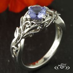 Custom 14kt white gold mounting 4-leaf prong holding a cushion cut sapphire center stone set at an angle. Pierced criss cross shank with curling leaf and vine filigree design on top face to 3/4 way down shank.