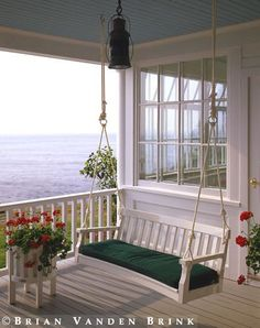 I love this cottage porch swing and the water view! #porchswing #porch #capecod www.capecodrelo.com