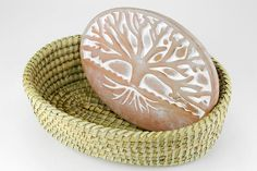 The Tree of Life Bread Warmer & Basket features a terra cotta warmer which is deeply incised with the Tree of Life, and sits within a handwoven kaisa grass basket with palm wrap.