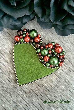 Brošňa v zelených, tehlových a hnedých farbách v tvare srdca. Brošňa je ručne šitá, dozdobená korálikmi v hornej časti. Komponenty v mosadznej farbe. Na hornej strane je filc, s brošňovým mostíkom ...